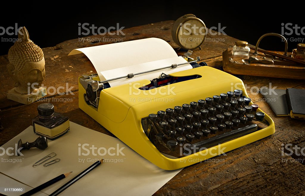 Vintage typewriter above an old wooden desk with old stationary stock photo