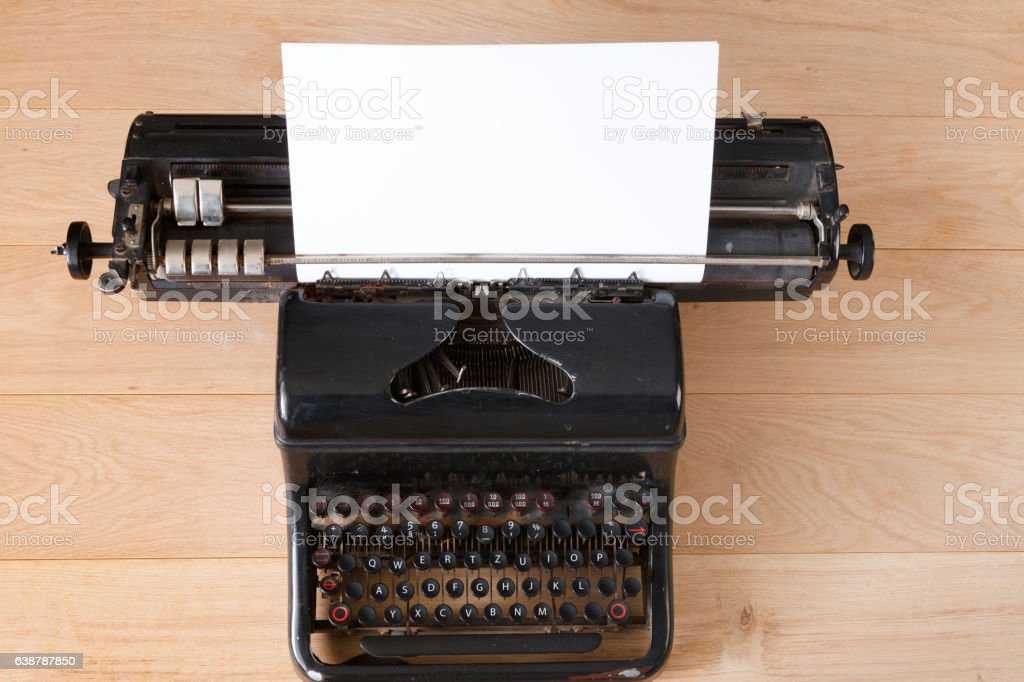 Vintage typewriter with paper sheet on wooden table top view. Old...