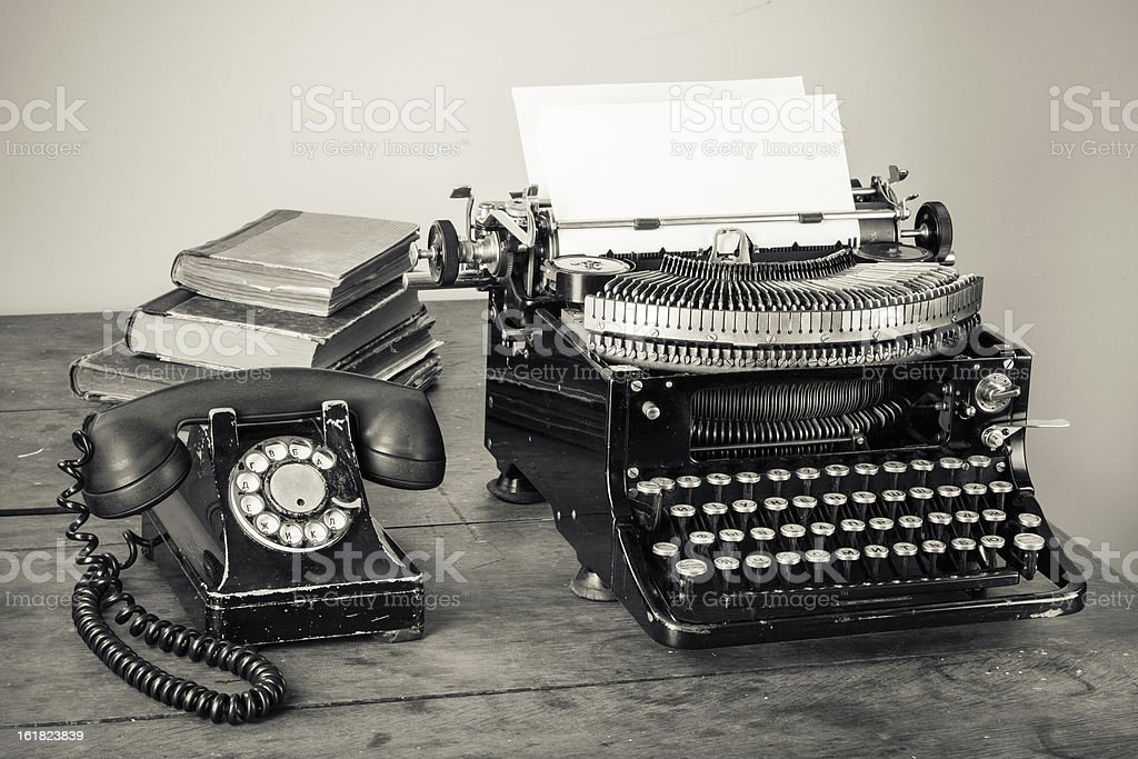 Vintage typewriter, telephone, old books on table desaturated photo stock photo