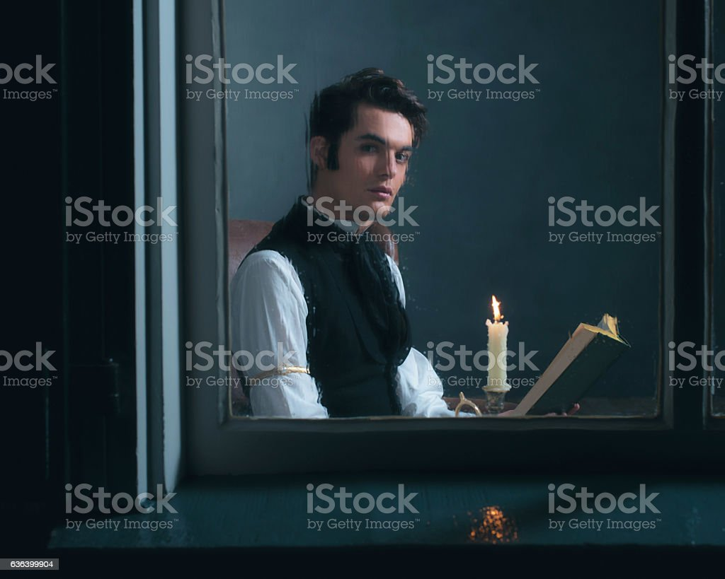Vintage victorian man sitting by rainy window reading book. stock photo