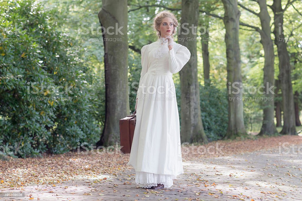 Vintage victorian woman holding suitcase standing in avenue. stock photo