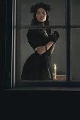 Vintage victorian woman in black dress standing behind window.