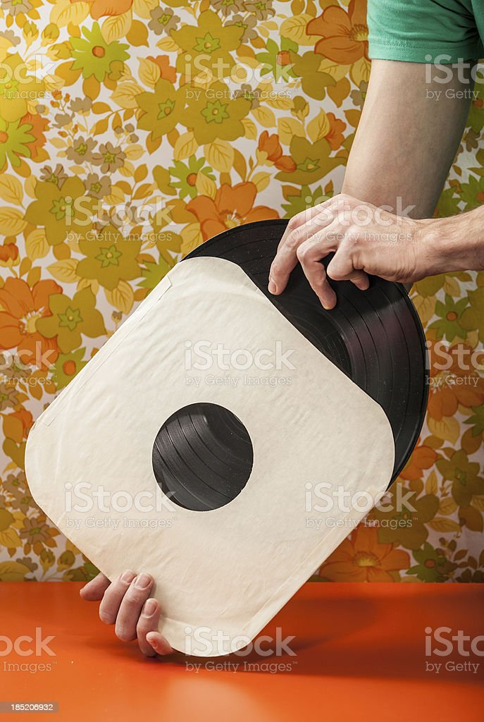 Vintage Vinyl Record Being Removed from Paper Cover royalty-free stock photo