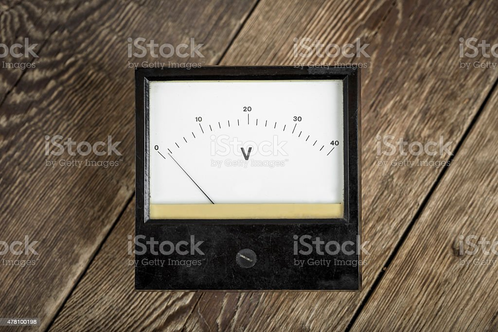 Vintage voltage meter on wooden table stock photo