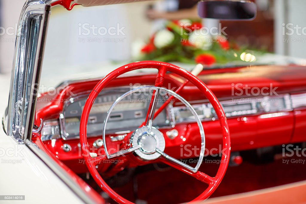 Vintage wedding car in red with bride flower bouquet stock photo