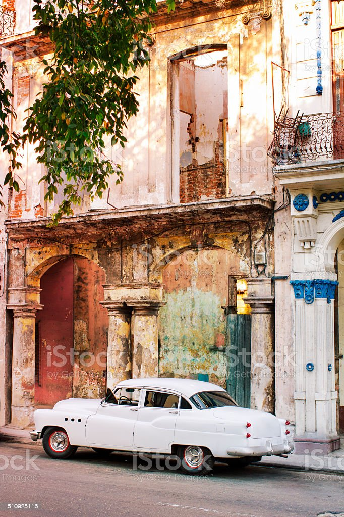 Vintage white car in colourful Cuban street stock photo