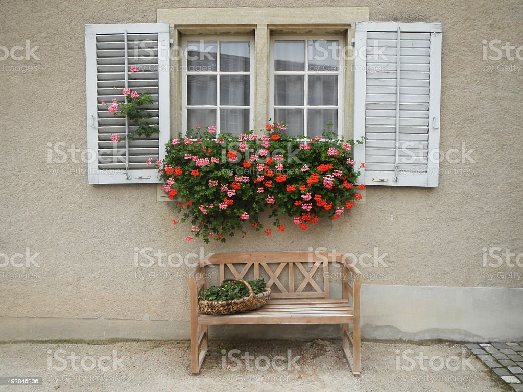 Vintage window with flowers and shutters in Switzerland stock photo
