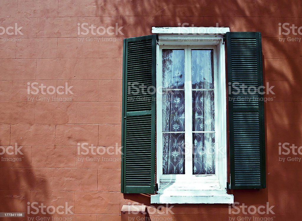 vintage window with green shutters and an orange wall royalty-free stock photo