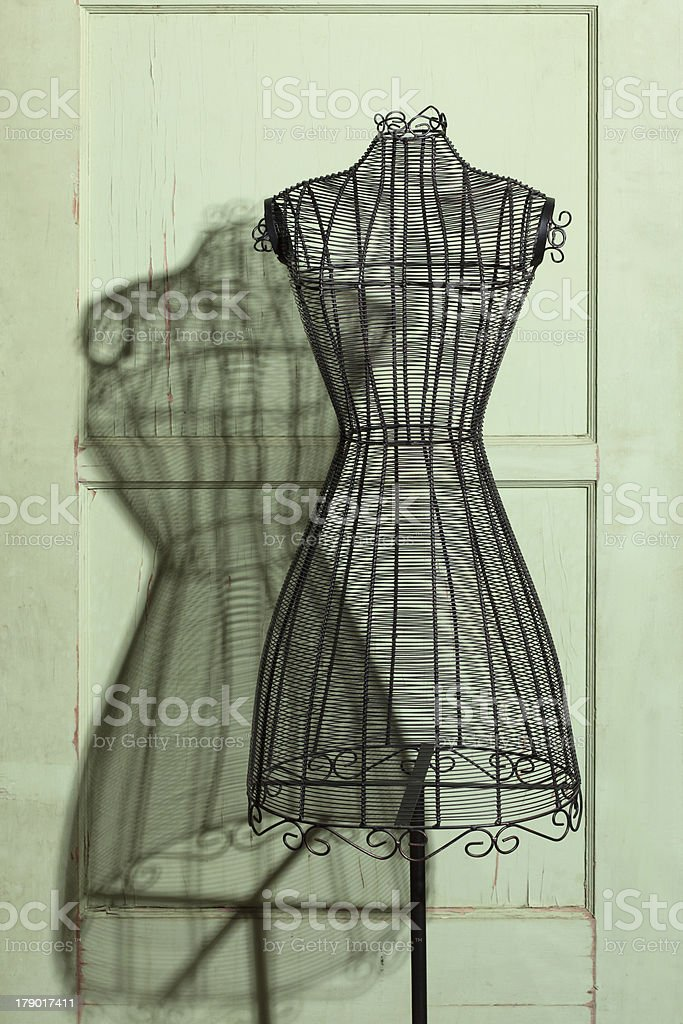 Vintage wire dress form casting shadow on a door stock photo