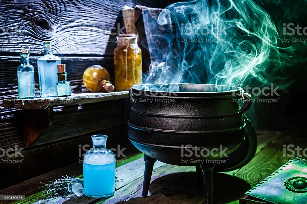 Vintage witcher cauldron with blue smoke and potions for Halloween stock photo