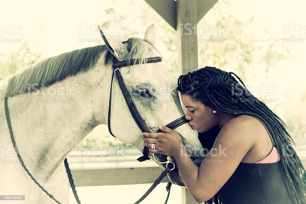 Vintage woman kissing horse stock photo