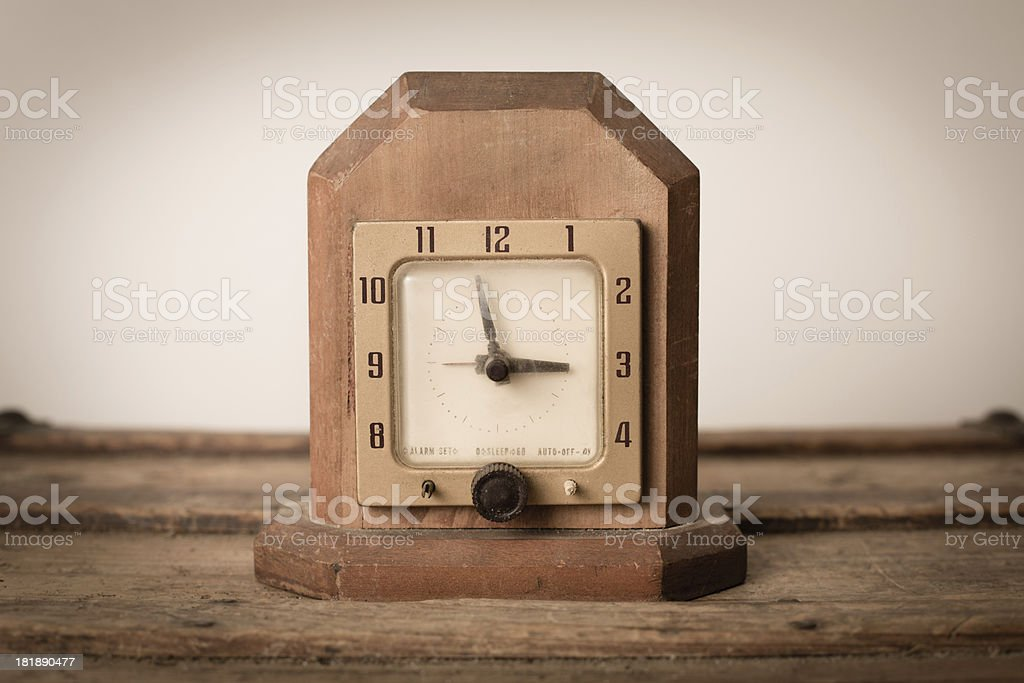 \'Close up color image of a vintage wood clock,sitting on wood trunk....