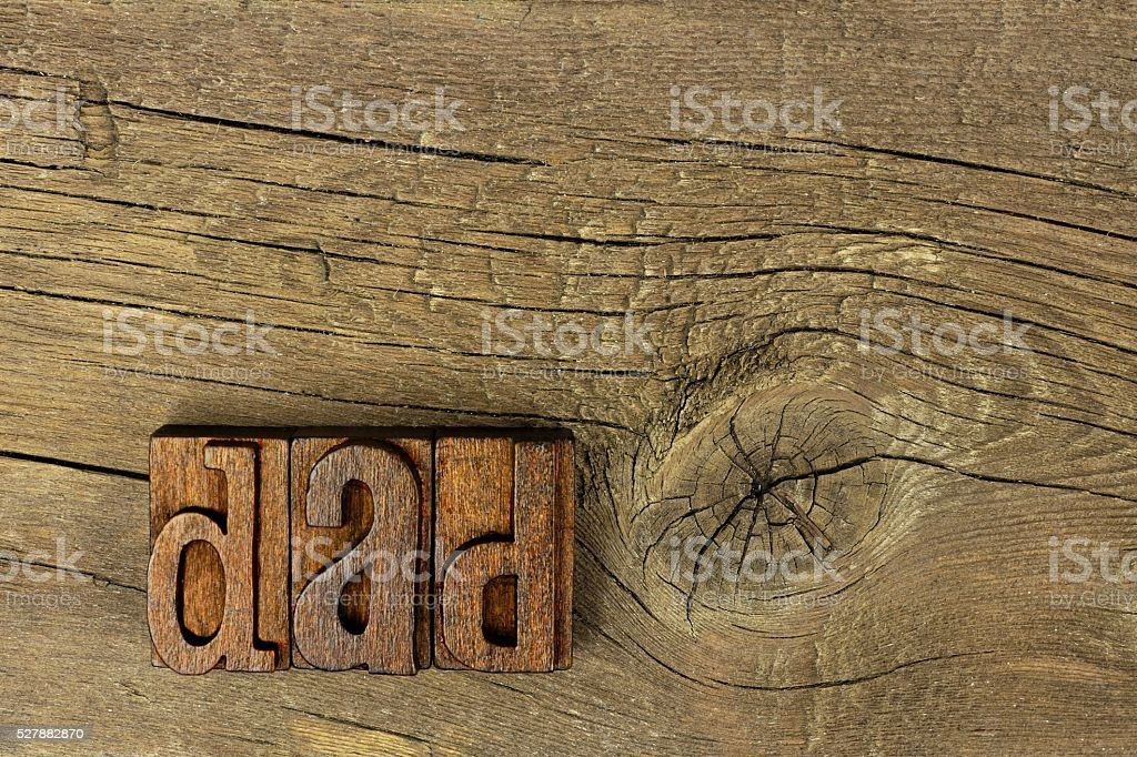 DAD vintage wood letters on a rustic wooden background stock photo