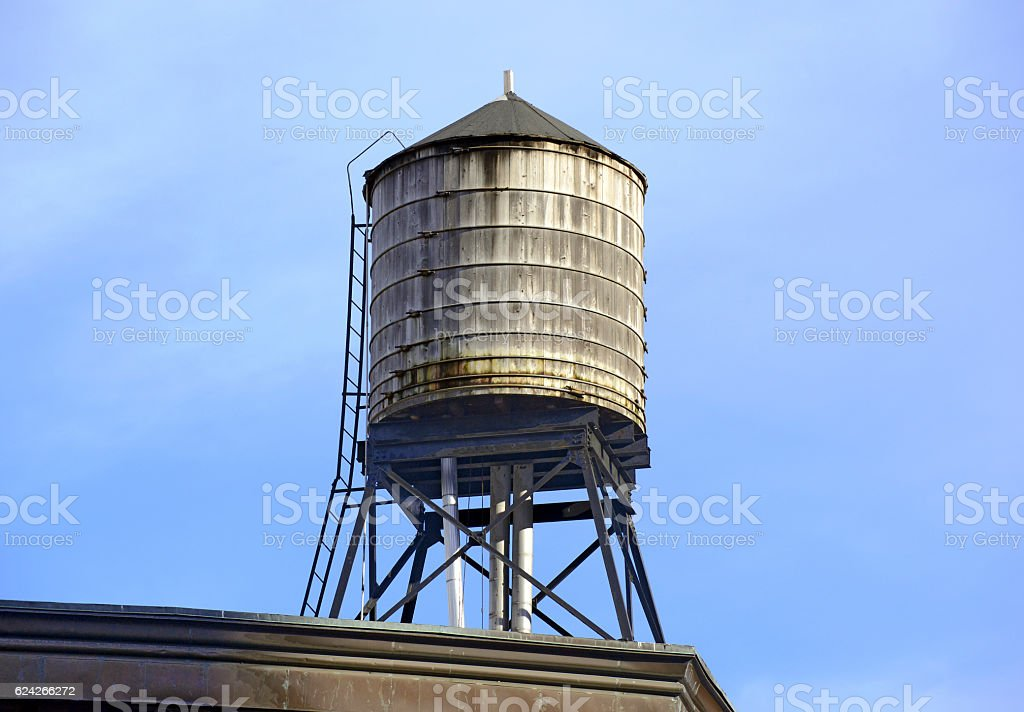 Vintage wooded water tank on roof of apartment building stock photo