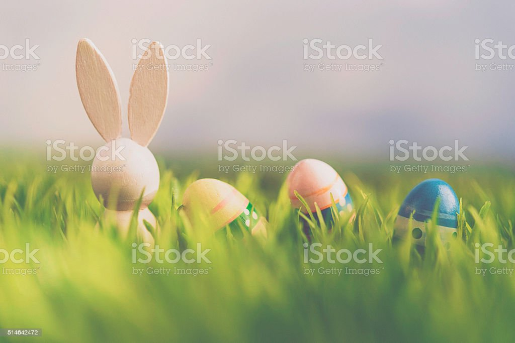 Vintage wooden bunny with Easter eggs in grass stock photo