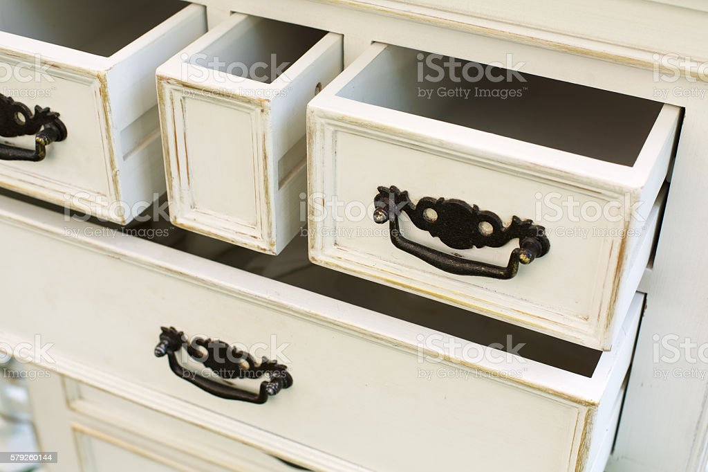 Vintage wooden chest of drawers with black metal handles open stock photo