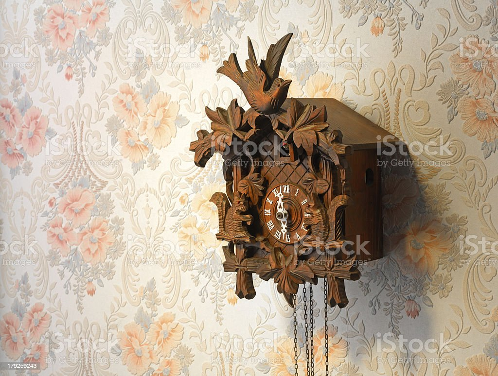 Vintage wooden cuckoo clock over a rose-pattern wall stock photo