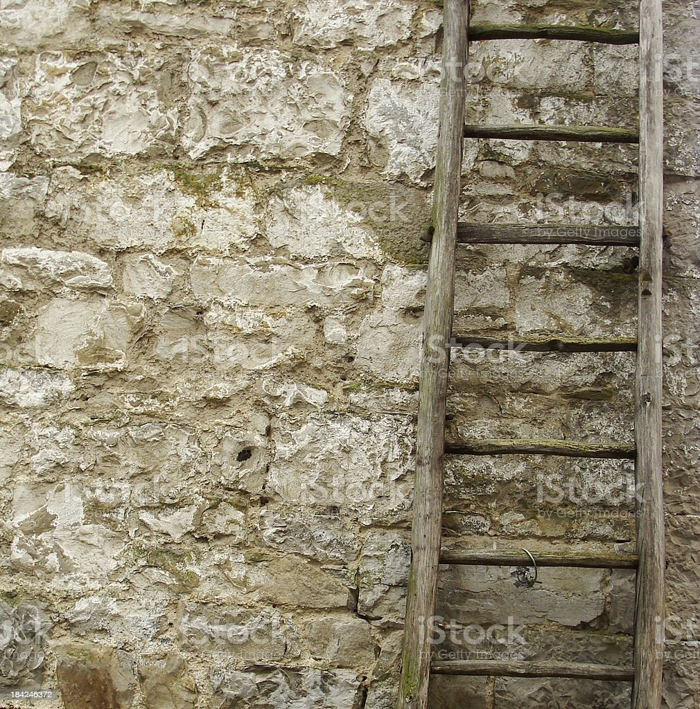 vintage wooden ladder in front of an old stone wall royalty-free stock photo