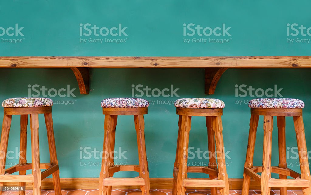 Vintage wooden stool chair on green background restaurant stock photo