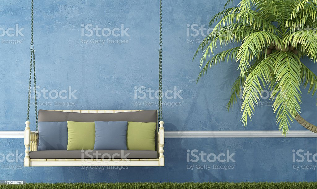 Vintage wooden swing against blue wall royalty-free stock photo