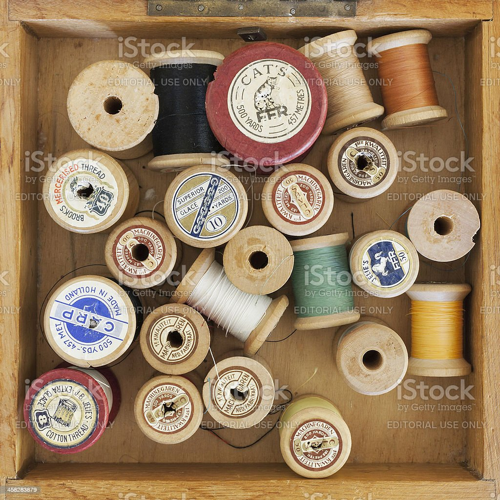 Vintage wooden thread spools collection in old Dutch sewing box. royalty-free stock photo