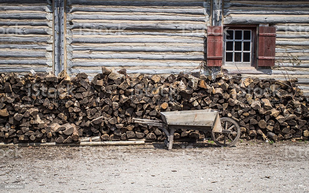 Vintage Wooden Wheelbarrow And Firewood stock photo