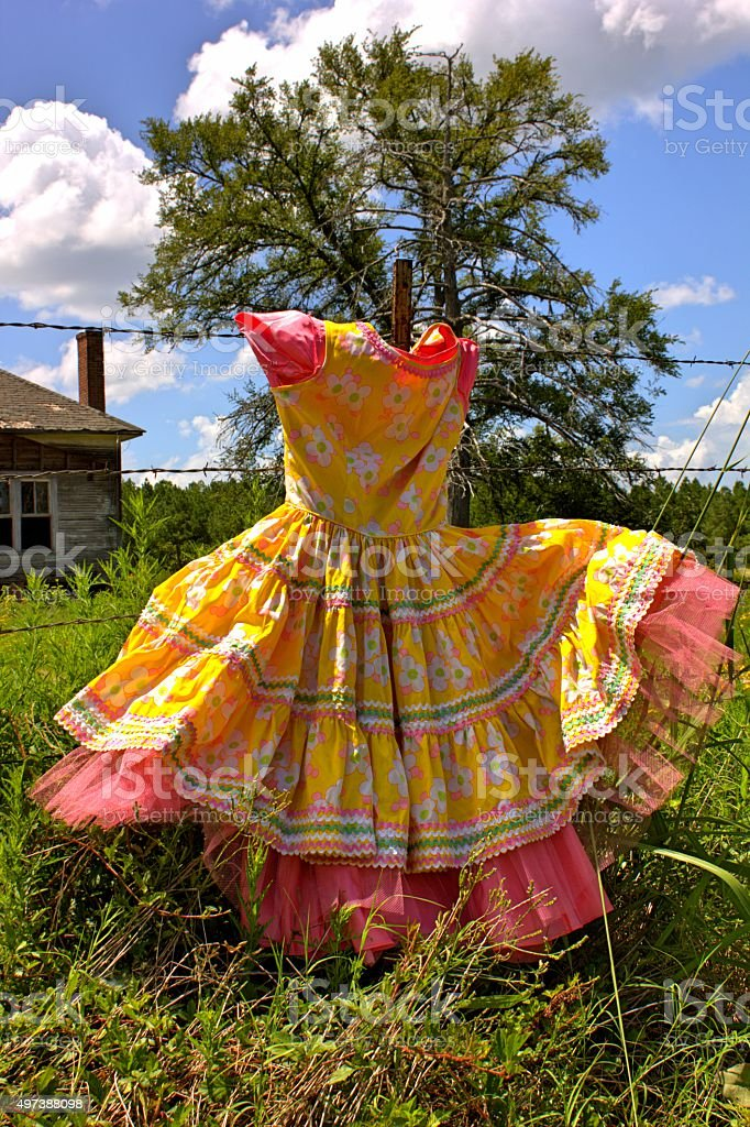 Vintage Yellow and Pink Dress in Field Against Blue Sky stock photo