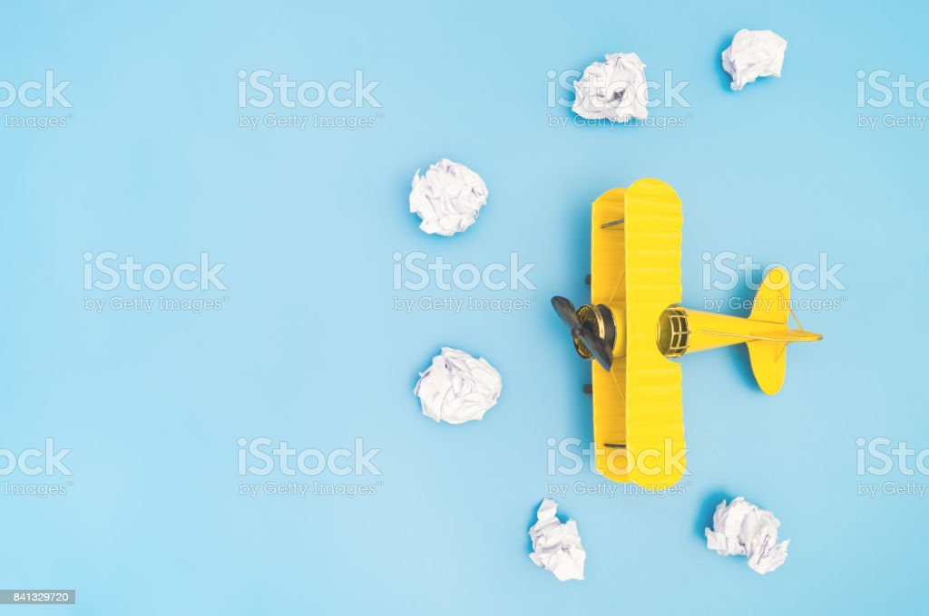 Vintage yellow metal toy plane and paper cloud on blue copy space stock photo
