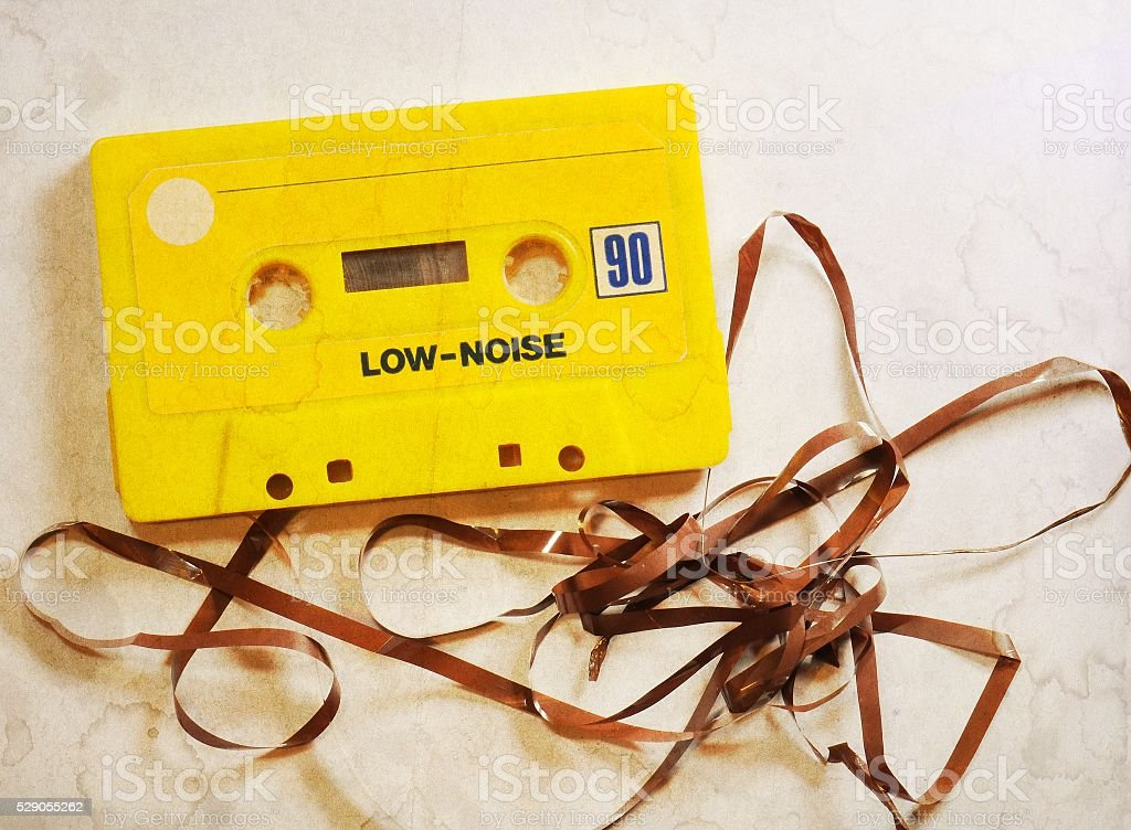Vintage yellow musicassette with damaged tape. Selective focus. stock photo