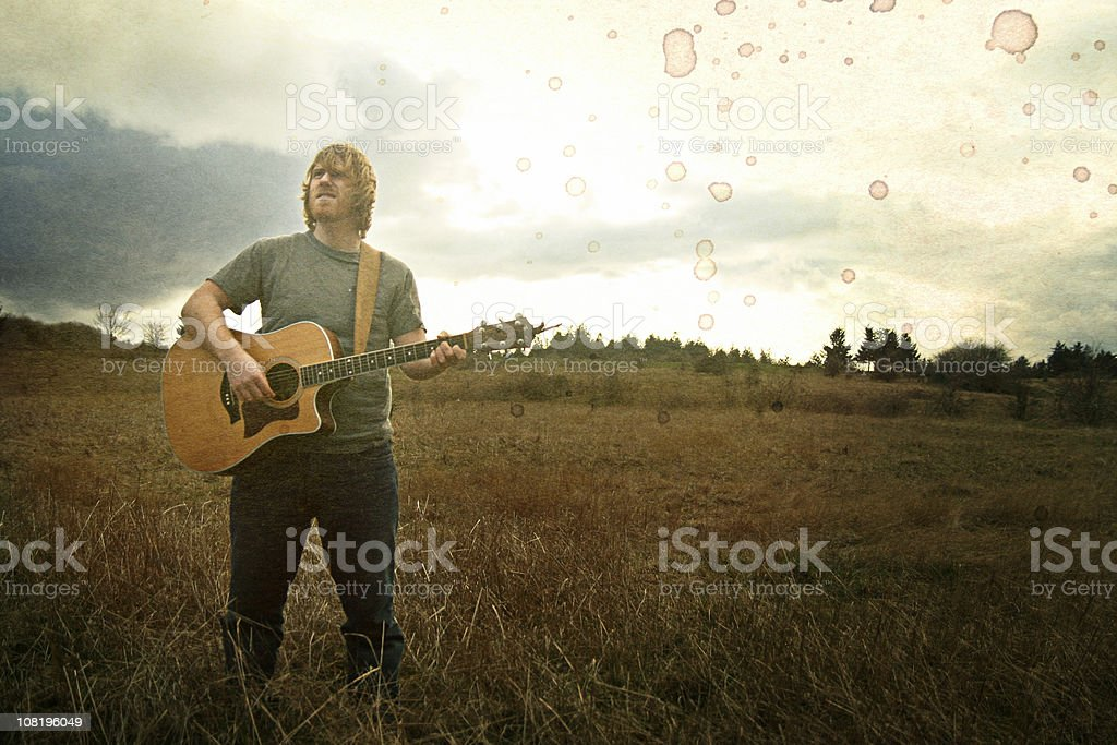 Vintage Young Guitarist in Field royalty-free stock photo