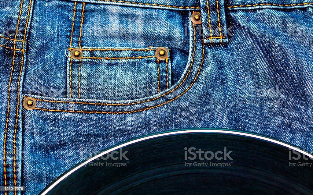 vinyl disc on jeans stock photo