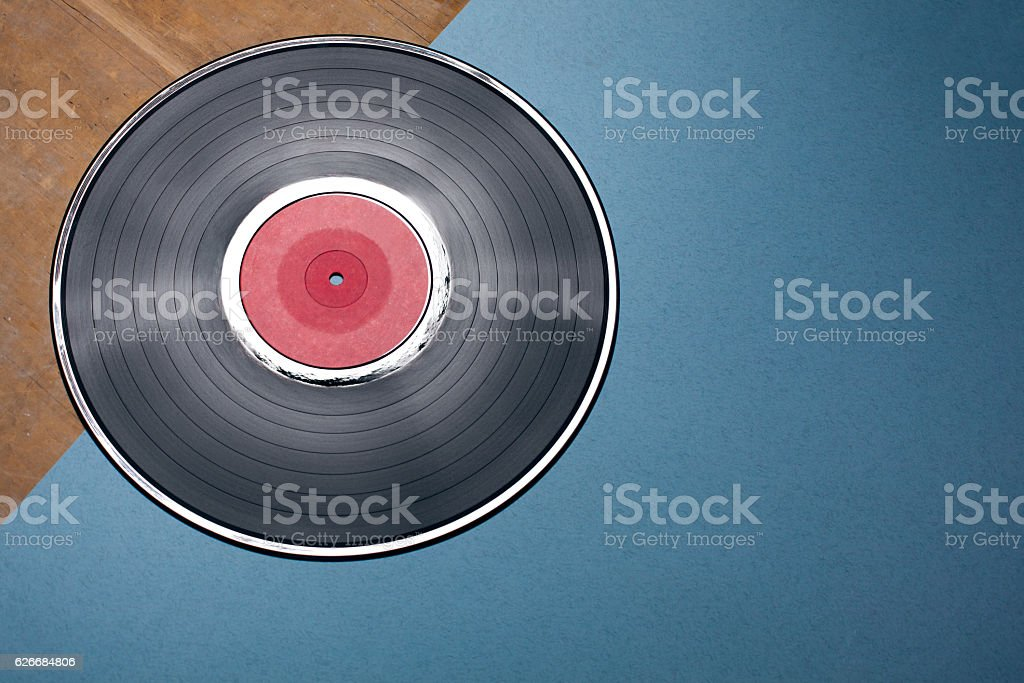 vinyl musical disc on blue and wooden background; stock photo