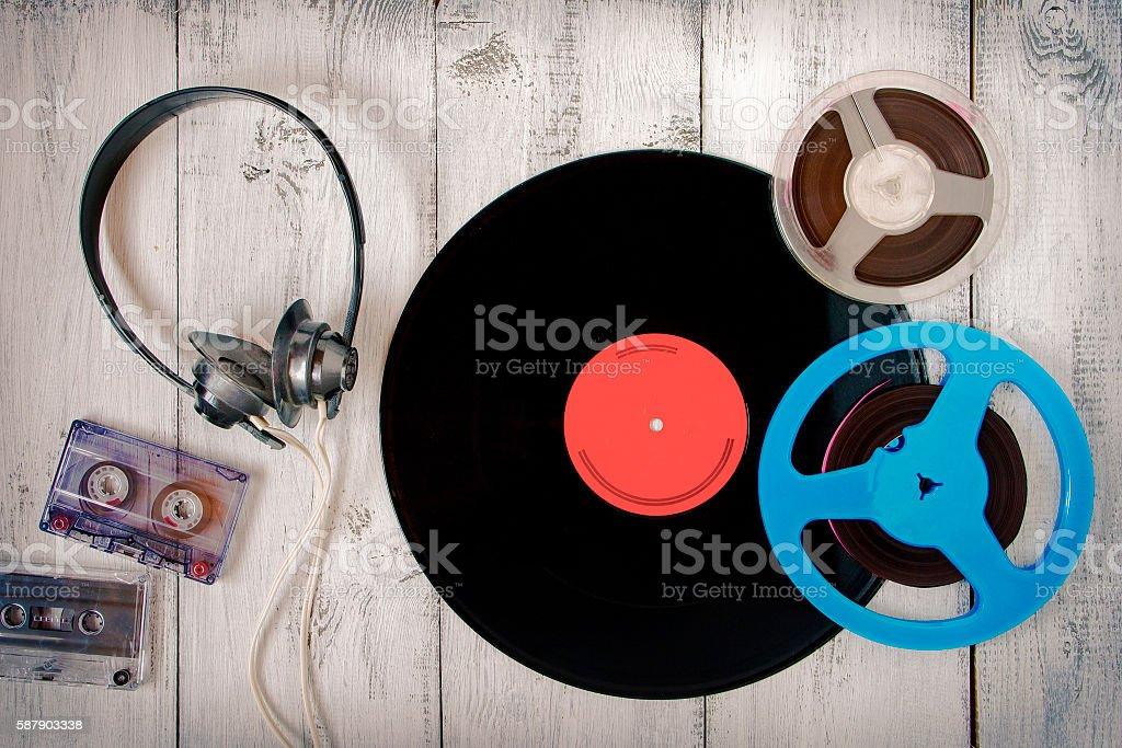 Vinyl record, cassette, reel tape and black audio headphones stock photo