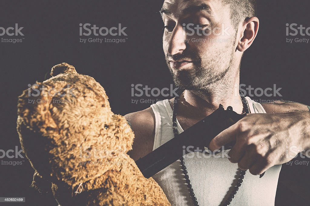 Violent man threating teddy bear with gun royalty-free stock photo