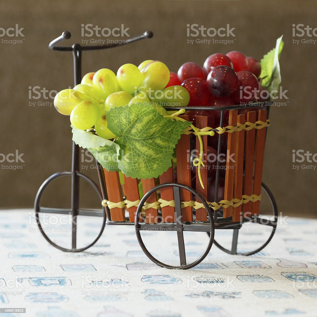 Violet and green Grapes in cute small bicycle royalty-free stock photo