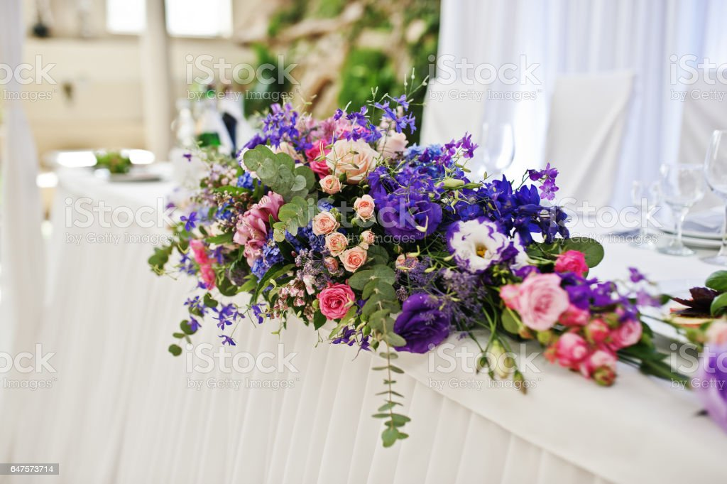 Violet and purple flowers at awesome wedding table. stock photo