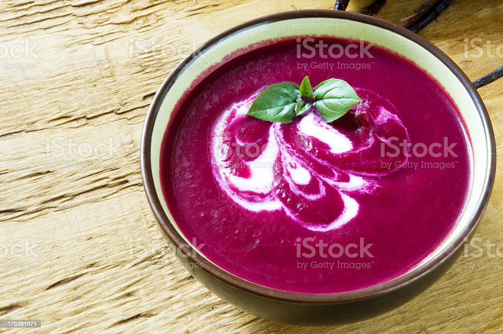 Violet colored beet soup in bowl on the counter stock photo