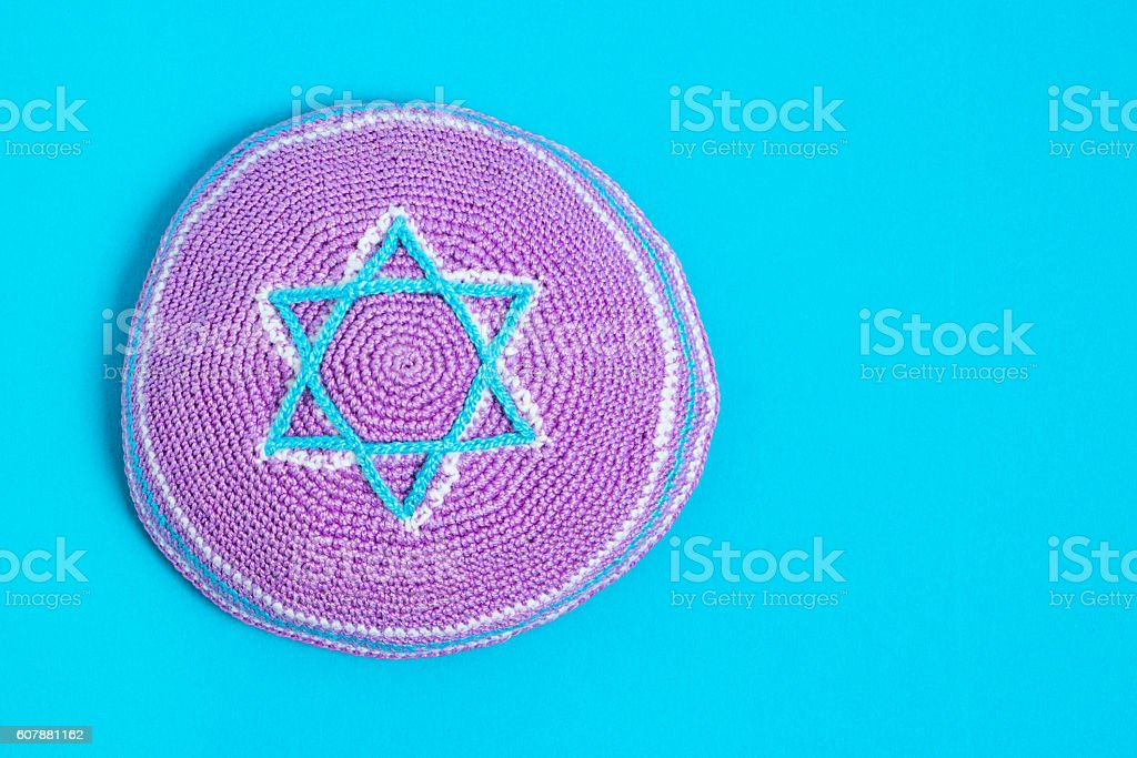 Violet kipa on a blue background, top view. Jewish New stock photo