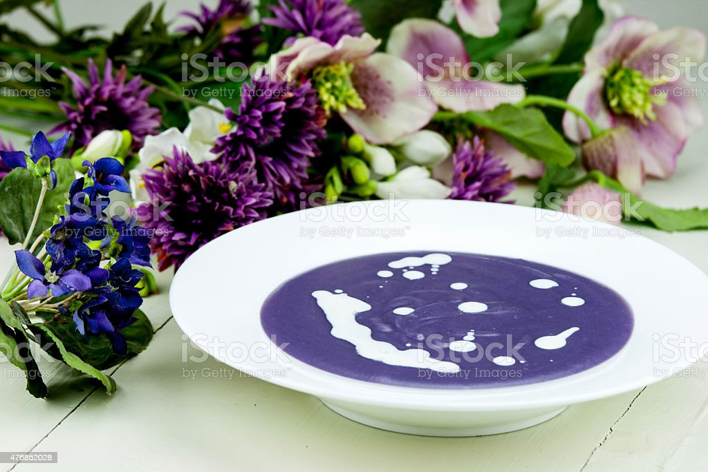Violet potato and leek soup with cream stock photo