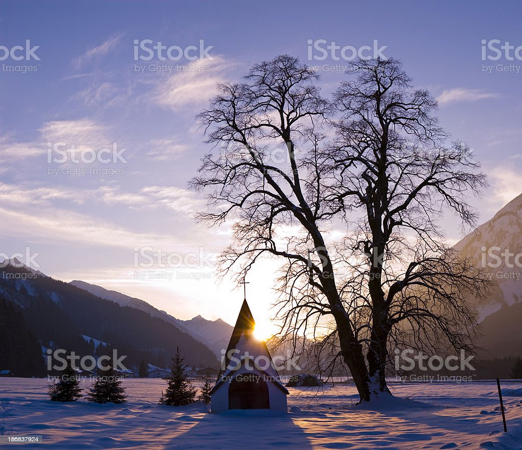 Violet Sunshine near little church and winter tree stock photo