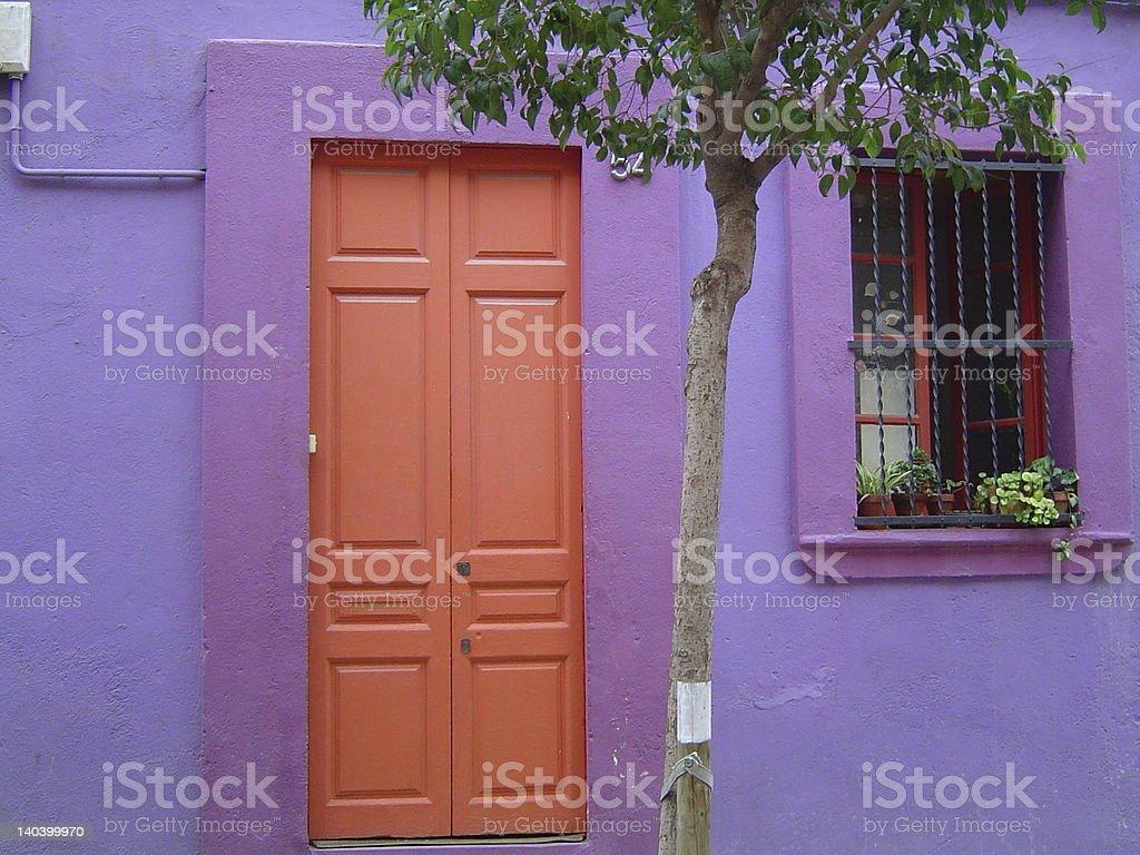 violet wall with orange door stock photo