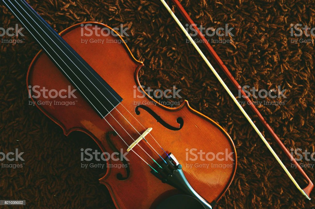 A violin and bow placed diagonally on a brown carpet, a horizontal shot stock photo