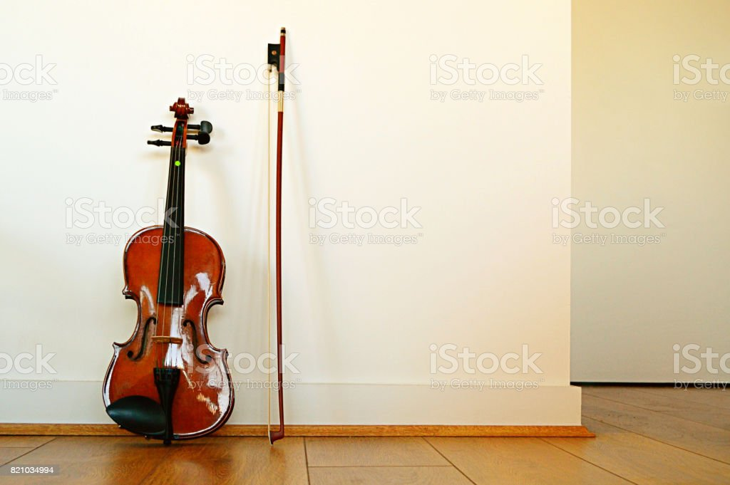 A violin and bow placed vertically on a wooden floor with white wall as background, a horizontal shot stock photo