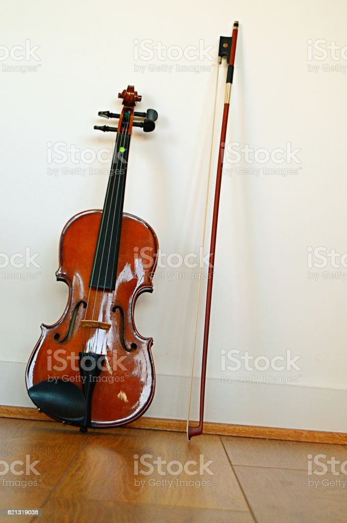 A violin and bow placed vertically on a wooden floor with white wall as background, a vertical shot stock photo