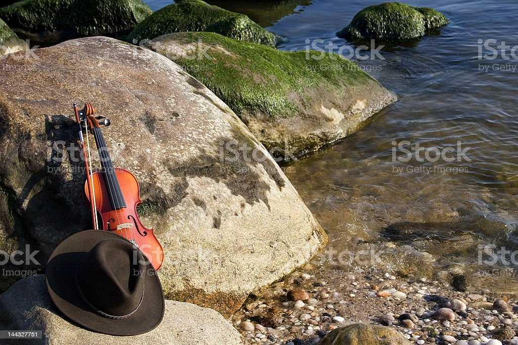 Violin and Cowboy Hat by the Seashore. stock photo