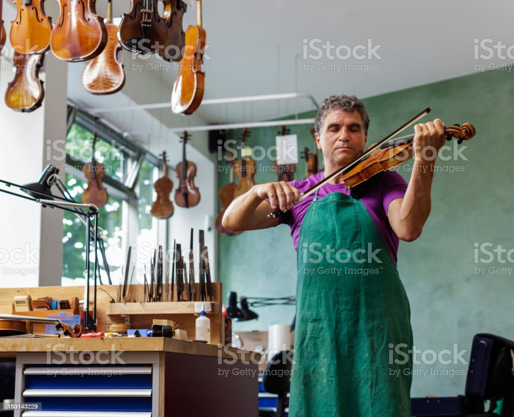 Violin Maker Testing an Instrument stock photo