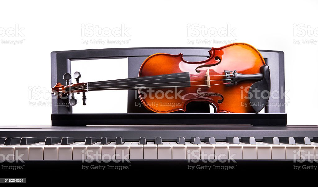 Violin on electronic piano music stand stock photo