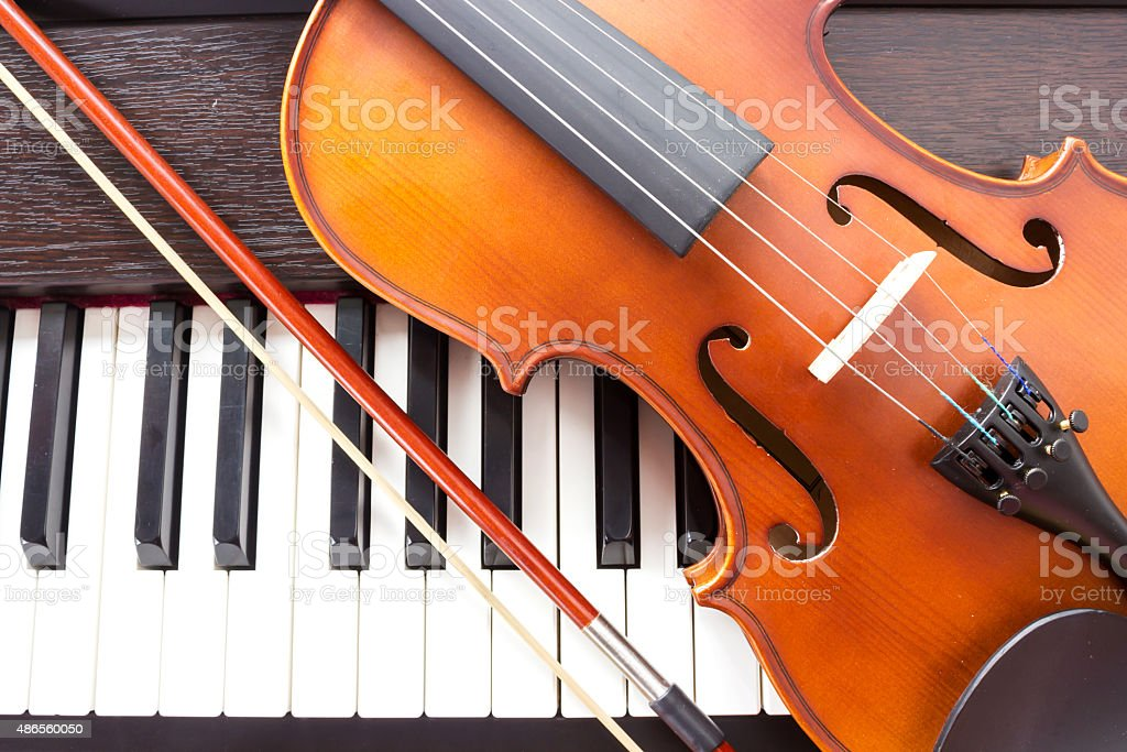 Violin on piano keyboard. stock photo