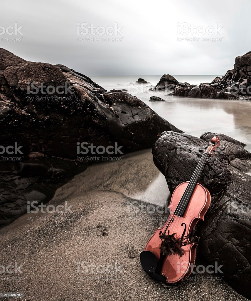 Violin on sandy beach with rocks royalty-free stock photo
