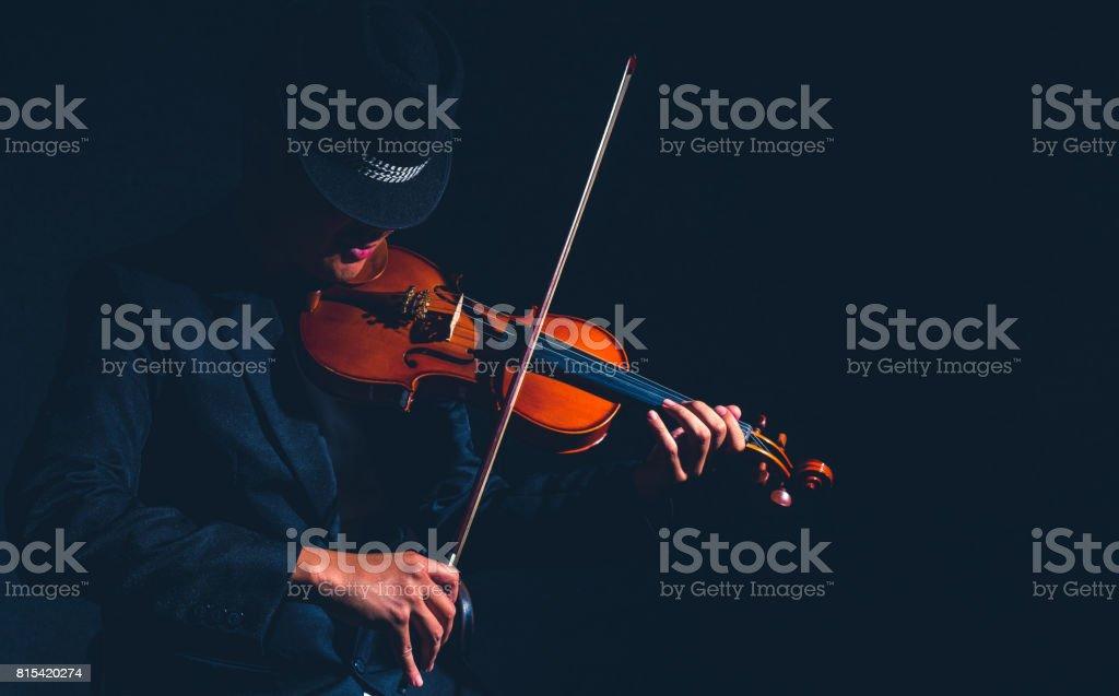 Violin player in dark studio, Musical concept stock photo